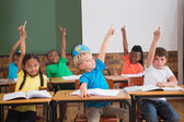Cute pupils raising their hands — Stock Photo