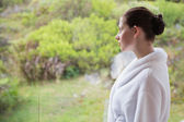 Woman wearing bathrobe against blurred plants — Stock Photo