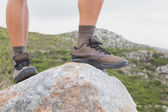 Low section of man on rock against mountain terrain — Stock Photo