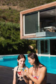 Women holding drinks by swimming pool — Foto de Stock