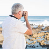 Casual mature man taking a photo of the sea — Stock Photo