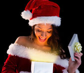 Pretty brunette in santa outfit opening gift — Stock Photo