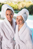 Smiling young women in bathrobes — Stock Photo