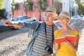 Happy tourist couple using guide book in the city — Stockfoto