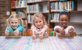 Cute pupils smiling in library — Stock Photo