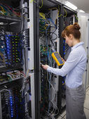 Technician using digital cable analyzer on server — ストック写真