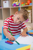 Little boy drawing at desk — Photo
