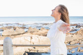 Casual woman smiling by the sea  — Stock Photo
