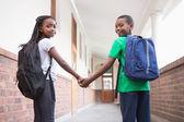 Pupils holding hands in corridor — Stock Photo
