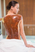 Attractive woman with chocolate back mask at spa center — Stock Photo