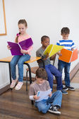 Classmates reading from notepads in classroom — Stock Photo
