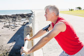 Fit mature man warming up on the pier — Stock Photo