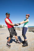 Fit mature couple rollerblading on the pier  — Stock Photo