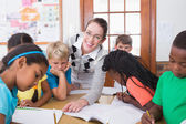 Teacher and pupils working at desk together — Stock Photo
