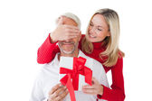 Smiling woman covering partners eyes and holding gift — Stock Photo