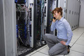 Technician talking on phone while analysing server — Stock Photo