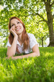 Pretty redhead relaxing in the park  — ストック写真
