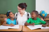 Pupils and teacher smiling at each other — Stock Photo