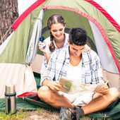 Couple looking at map outside their tent — Stock Photo