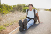 Hiking man sitting on countryside road — Stock Photo