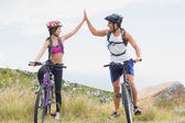 Athletic couple mountain biking while high fiving — Stock Photo