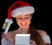Pretty redhead in santa outfit opening a gift — Stock Photo