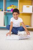 Boy on floor reading in classroom — Stock Photo