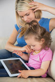 Mother and daughter using digital tablet on couch — Stock Photo