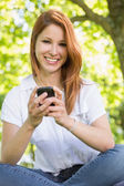 Redhead sending a text in the park — Stock Photo