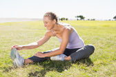 Fit mature woman warming up on the grass — Stock Photo