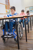 Disabled pupil writing in classroom — Stock Photo