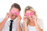 Attractive young couple holding pink hearts over eyes — Stock Photo