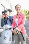 Happy senior couple posing with their moped — Stock Photo