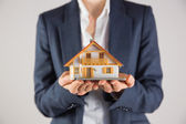 Businesswoman holding miniature model house — Stock Photo