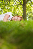 Pretty redhead lying on the grass — ストック写真