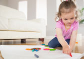 Little girl drawing in living room — Stock Photo