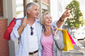 Happy mature couple walking with their shopping purchases — Stock Photo