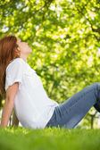 Pretty redhead relaxing in the park  — Stock fotografie
