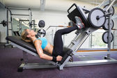 Side view of fit woman doing leg presses in gym — Stock Photo