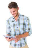 Przystojny młody człowiek za pomocą jego komputera typu tablet — Zdjęcie stockowe
