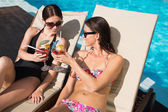 Women toasting drinks by swimming pool — Stock Photo
