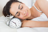 Beautiful woman sleeping in bed with alarm clock — Stock Photo