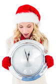 Festive blonde holding large clock — Stockfoto