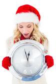 Festive blonde holding large clock — ストック写真