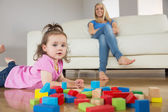 Girl playing with building blocks while mother on conch — Stock Photo