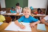 Alumnos escribiendo en mesa de salón de clases — Foto de Stock