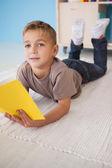 Little boy on floor reading in classroom — Stock Photo