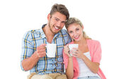 Attractive young couple sitting holding mugs — Foto de Stock