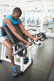 Young man lifting barbell in gym — Stok fotoğraf