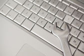 Pliers lying on silver keyboard — Stock Photo